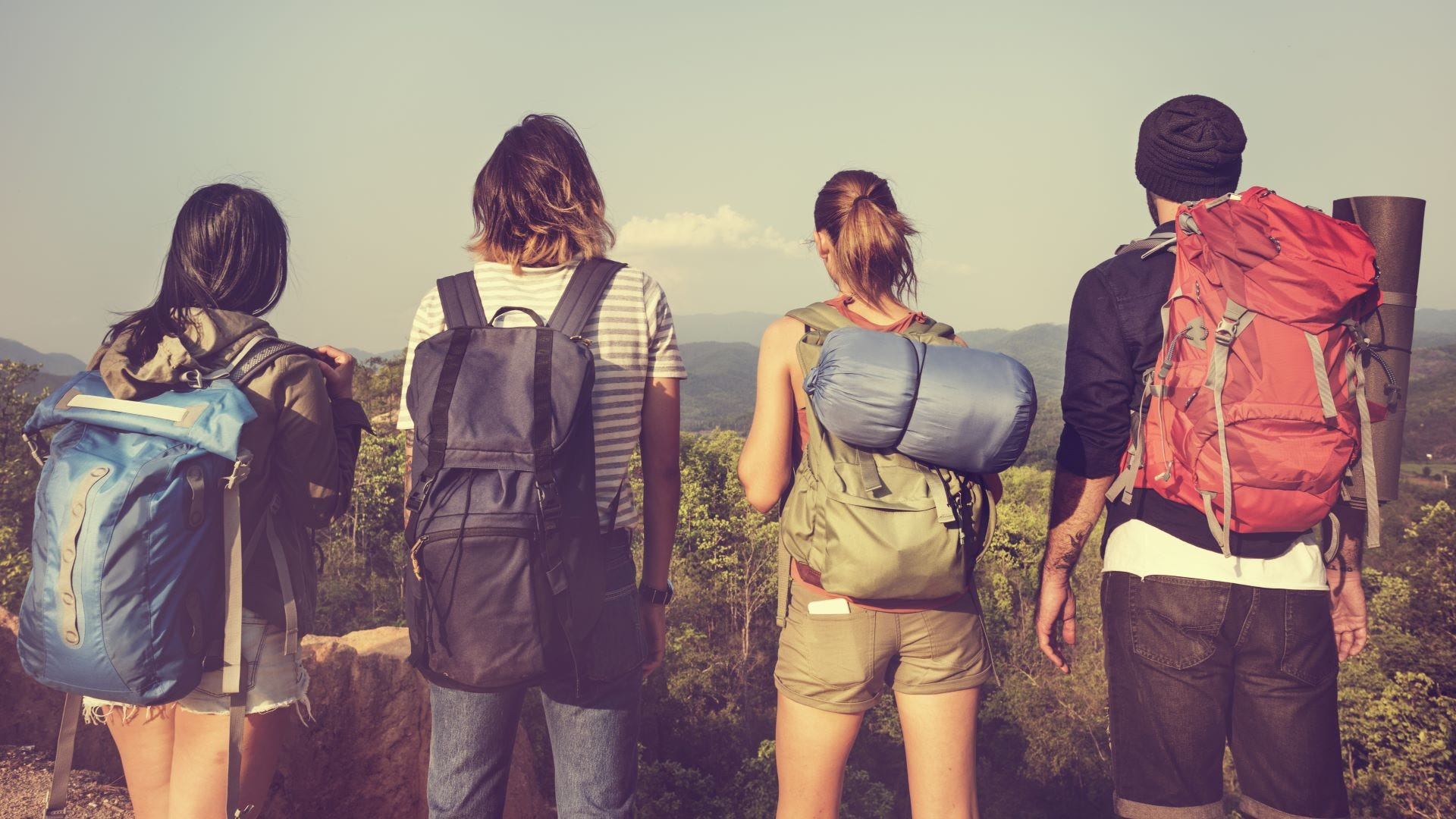 Four backpackers looking out over a mountain hiking trail.