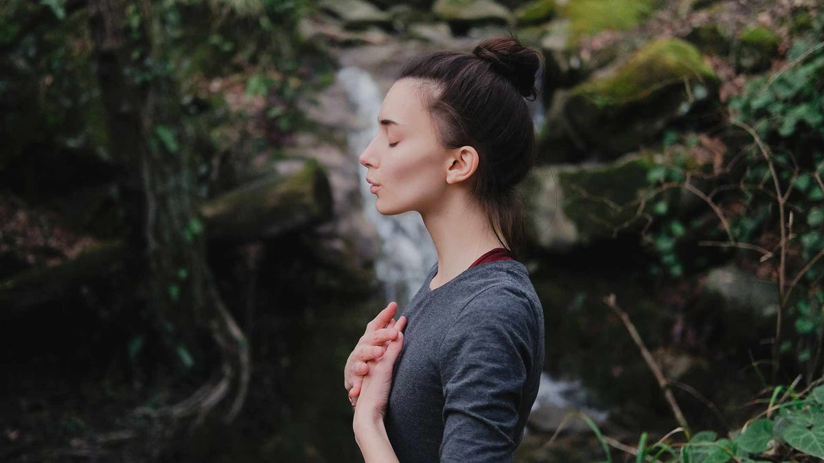 A woman taking a deep breath in a forest.