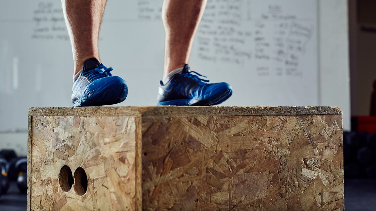 Closeup of athlete doing box jump at the gym.