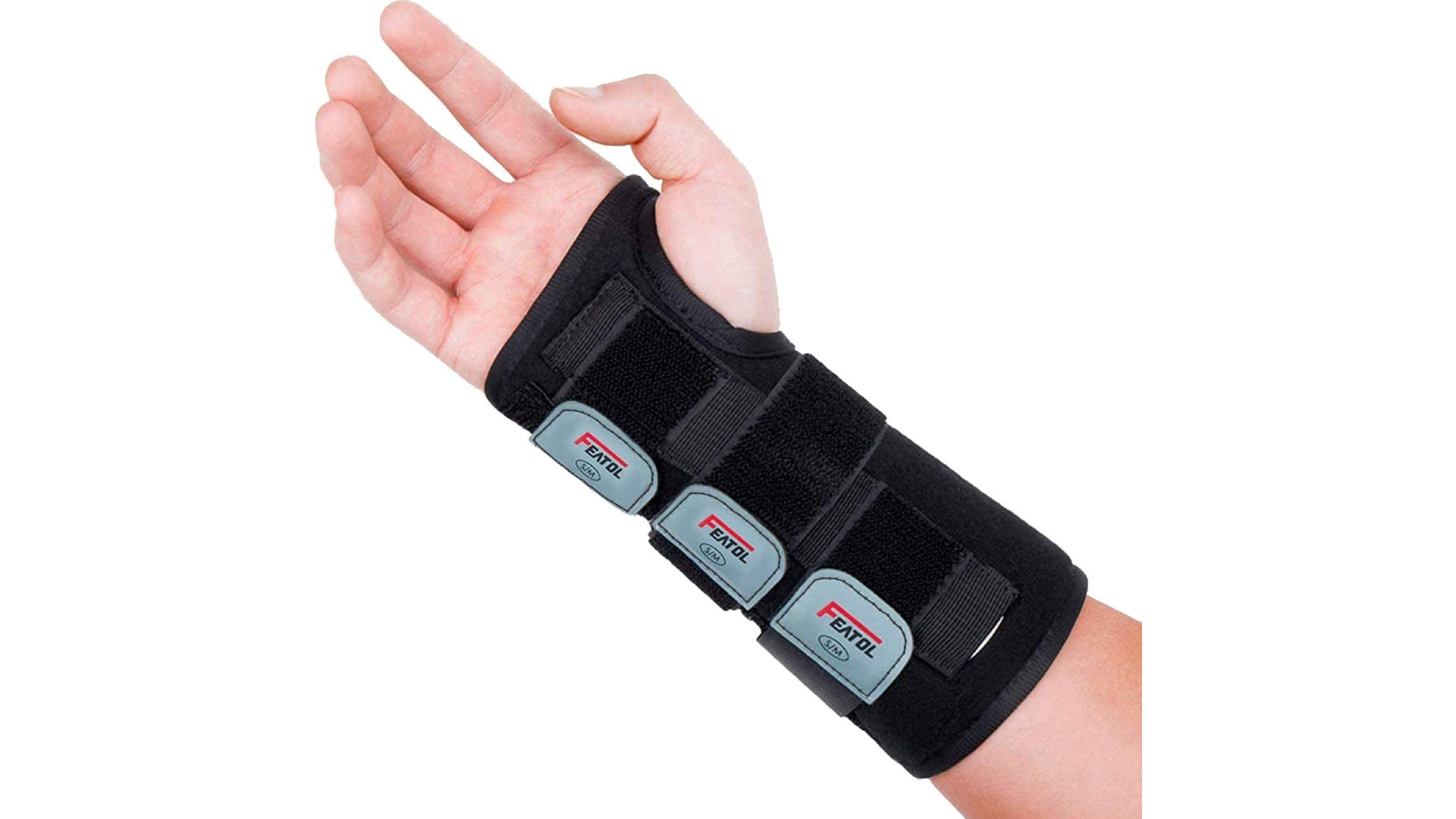A hand wearing a black wrist brace that wraps around the thumb and extends town the forearm.