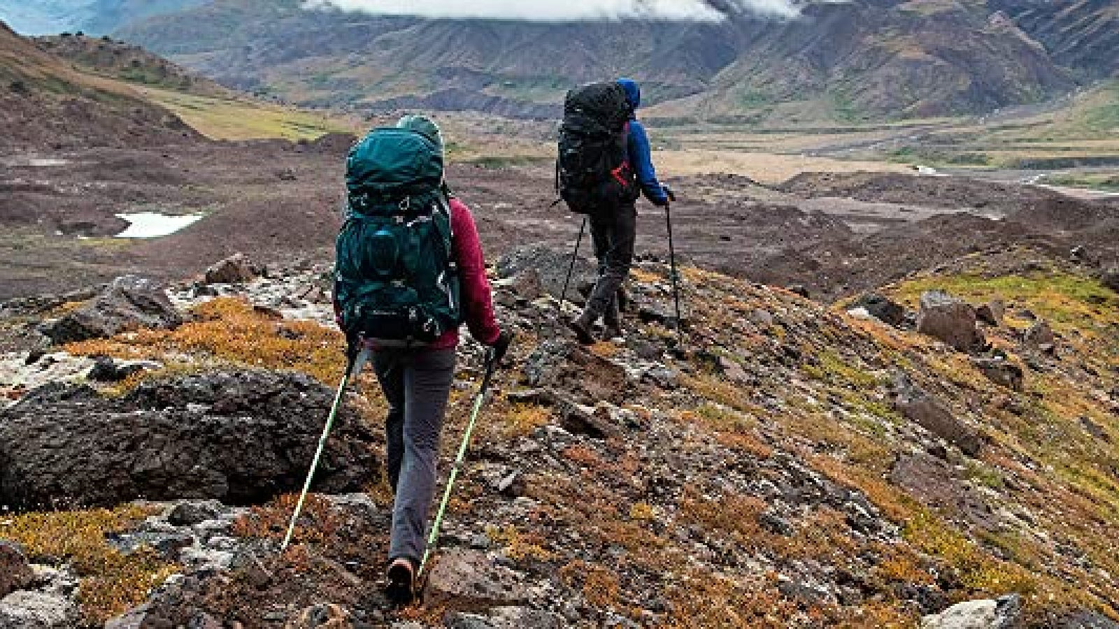 Two hikers hiking along the ridge of a trail while wearing their hiking packs.
