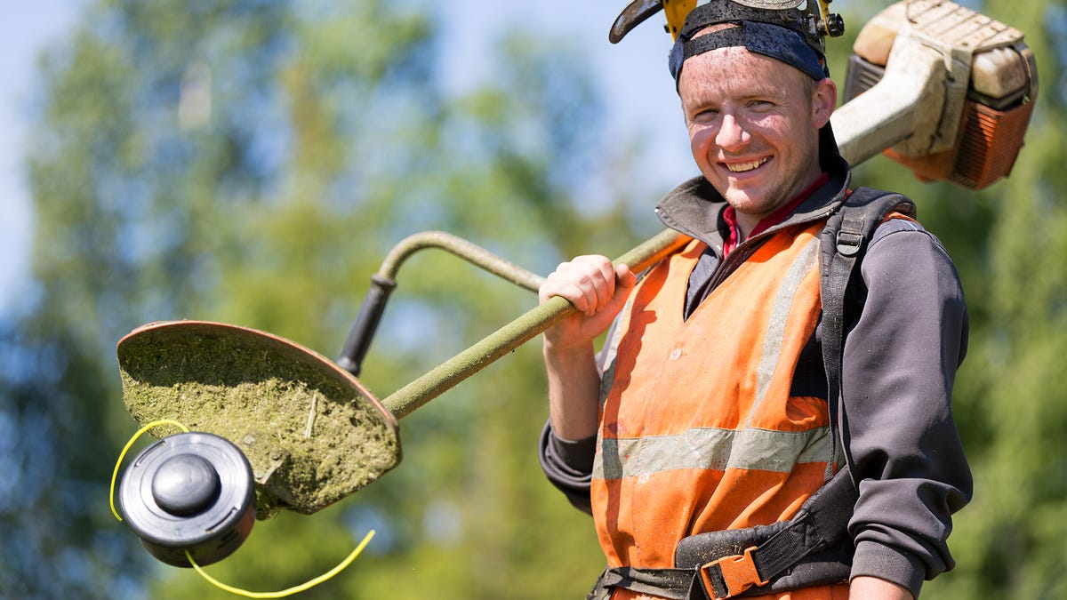 Portrait of a smiling gardener with gas grass trimmer equipment.