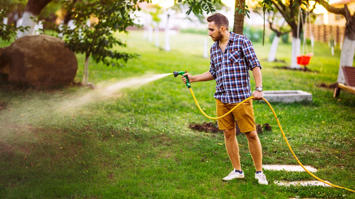 A man using water hose and spray nozzle to water the lawn.