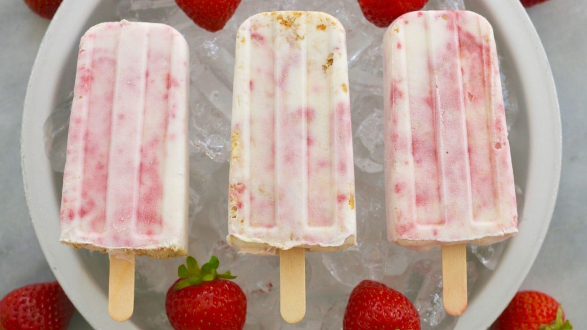 Three strawberry cheesecake popsicles