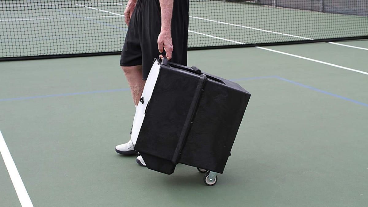 A person wheels a black tennis ball machine across a tennis court with their left hand.