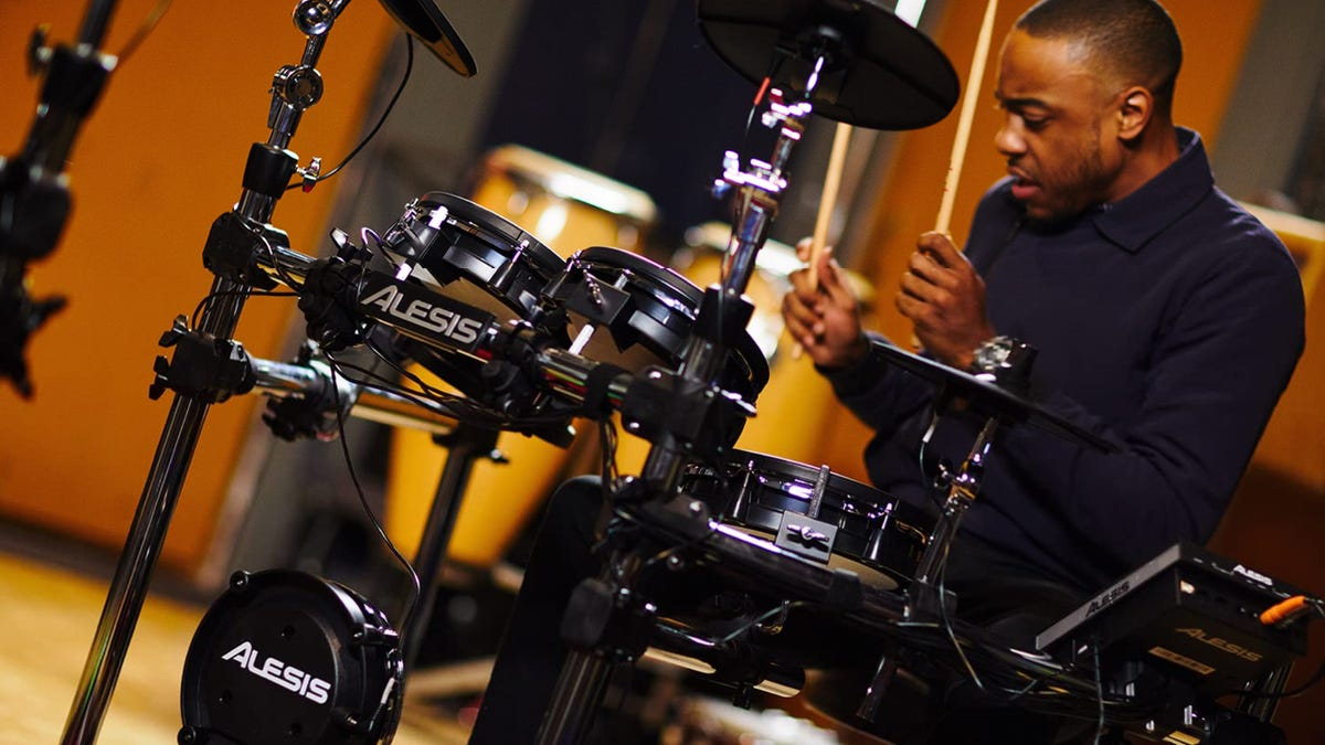A male drummer playing on an electronic drum set.