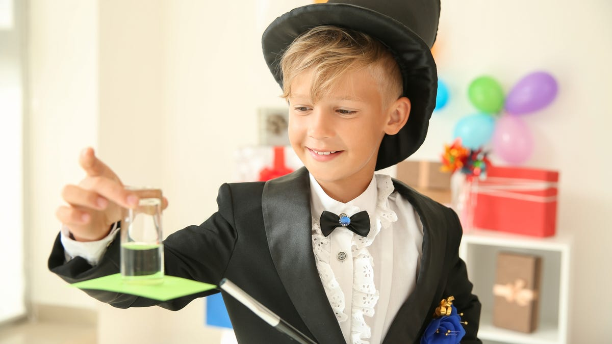 Young magician showing a trick indoors.