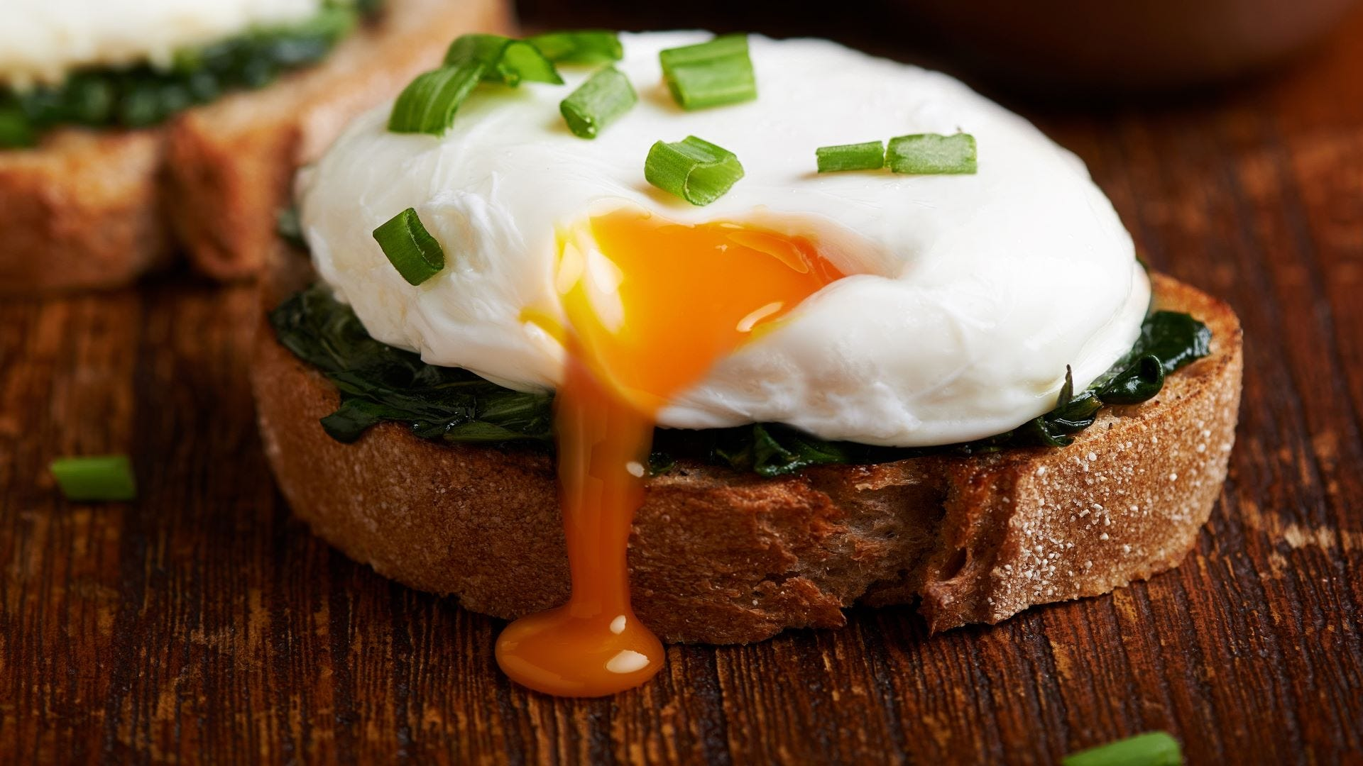 A poached egg on a piece of bread with spinach.