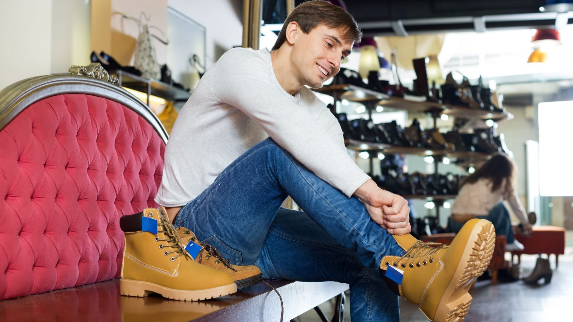 A man trying on hiking boots at a shoe store.