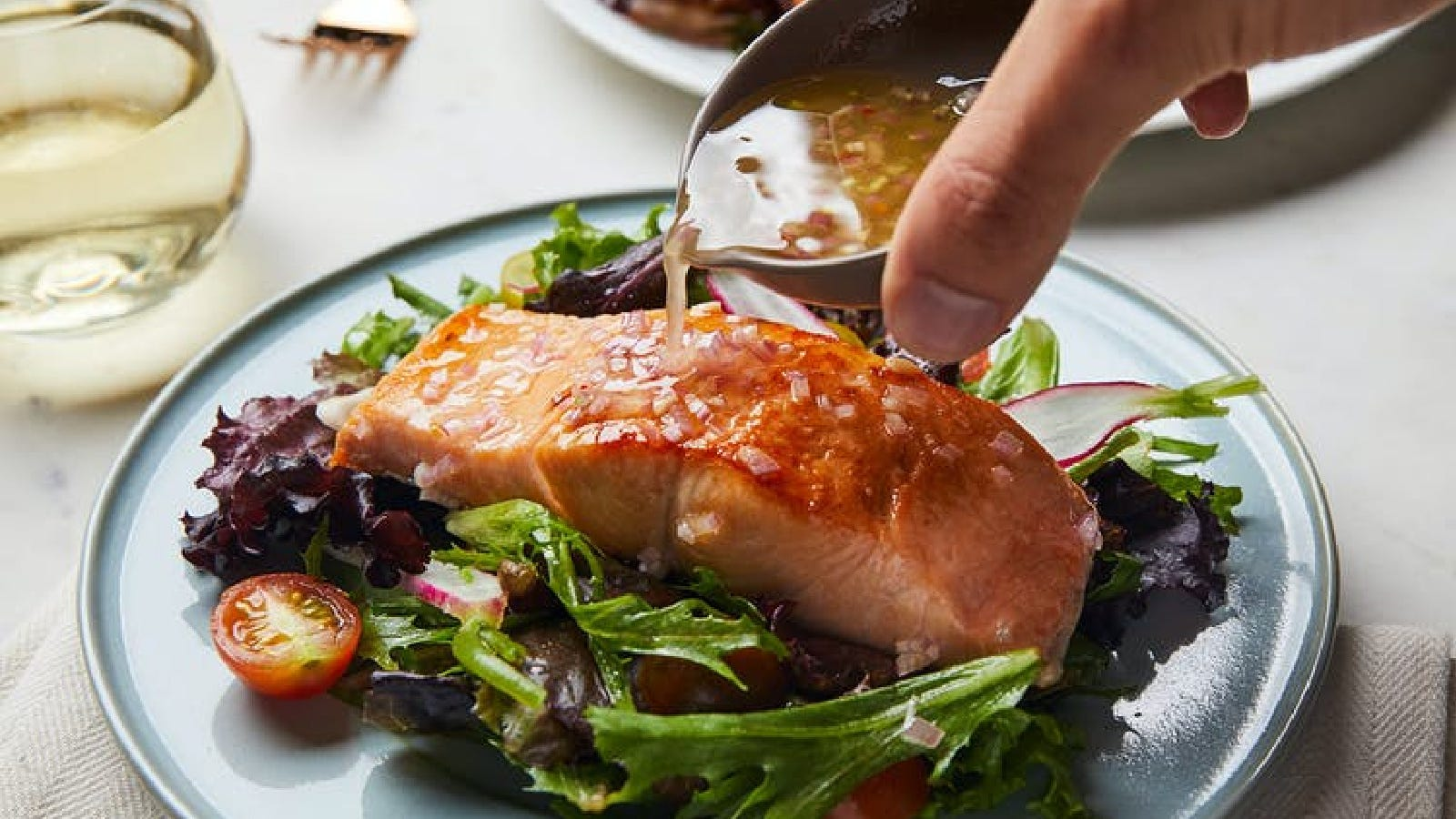 An image of a salmon salad being topped with a housemade pickle brine vinaigrette.