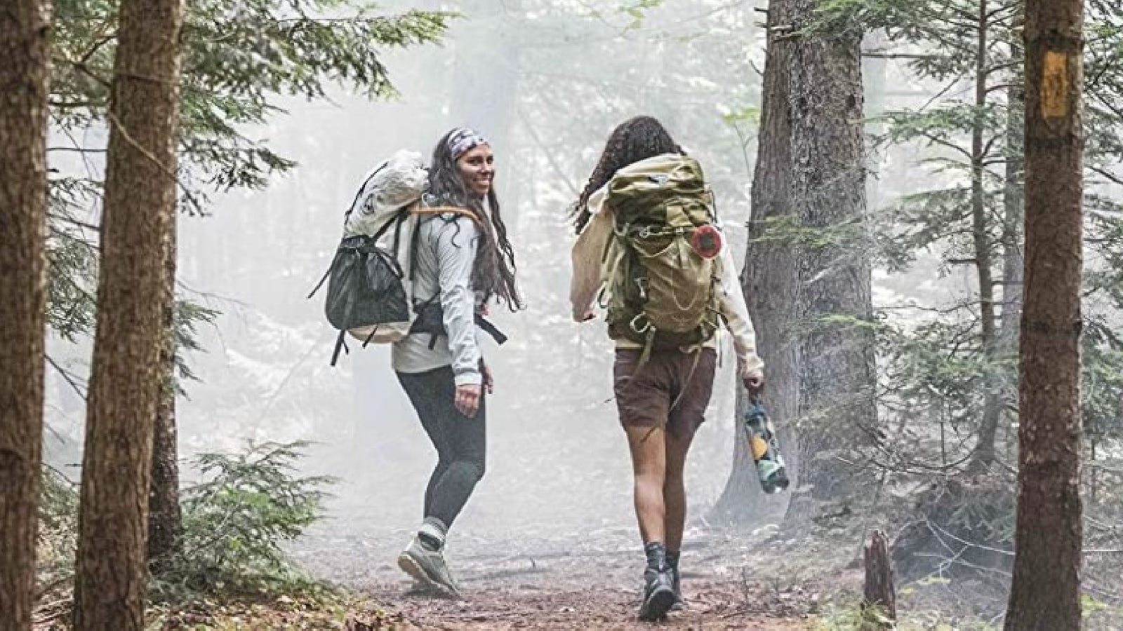 Two girls out hiking along a dense trail wearing their comfortable and sturdy Merrell hiking boots.