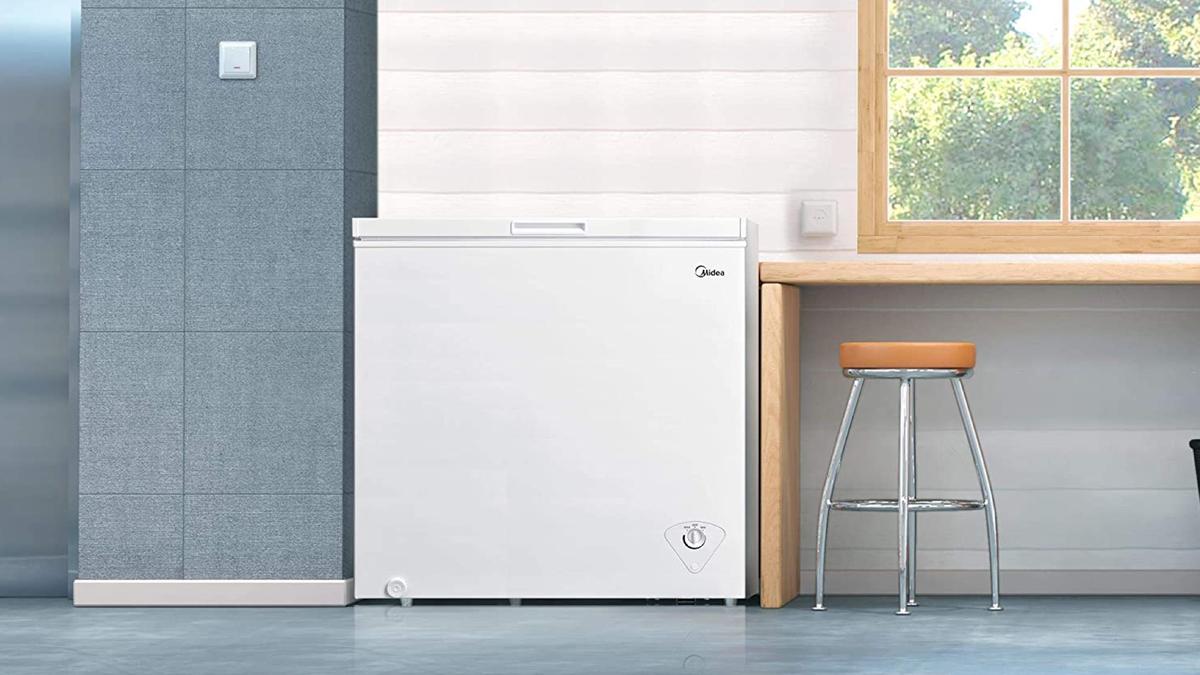 large, rectangular, white chest freezer in a light, airy, modern garage