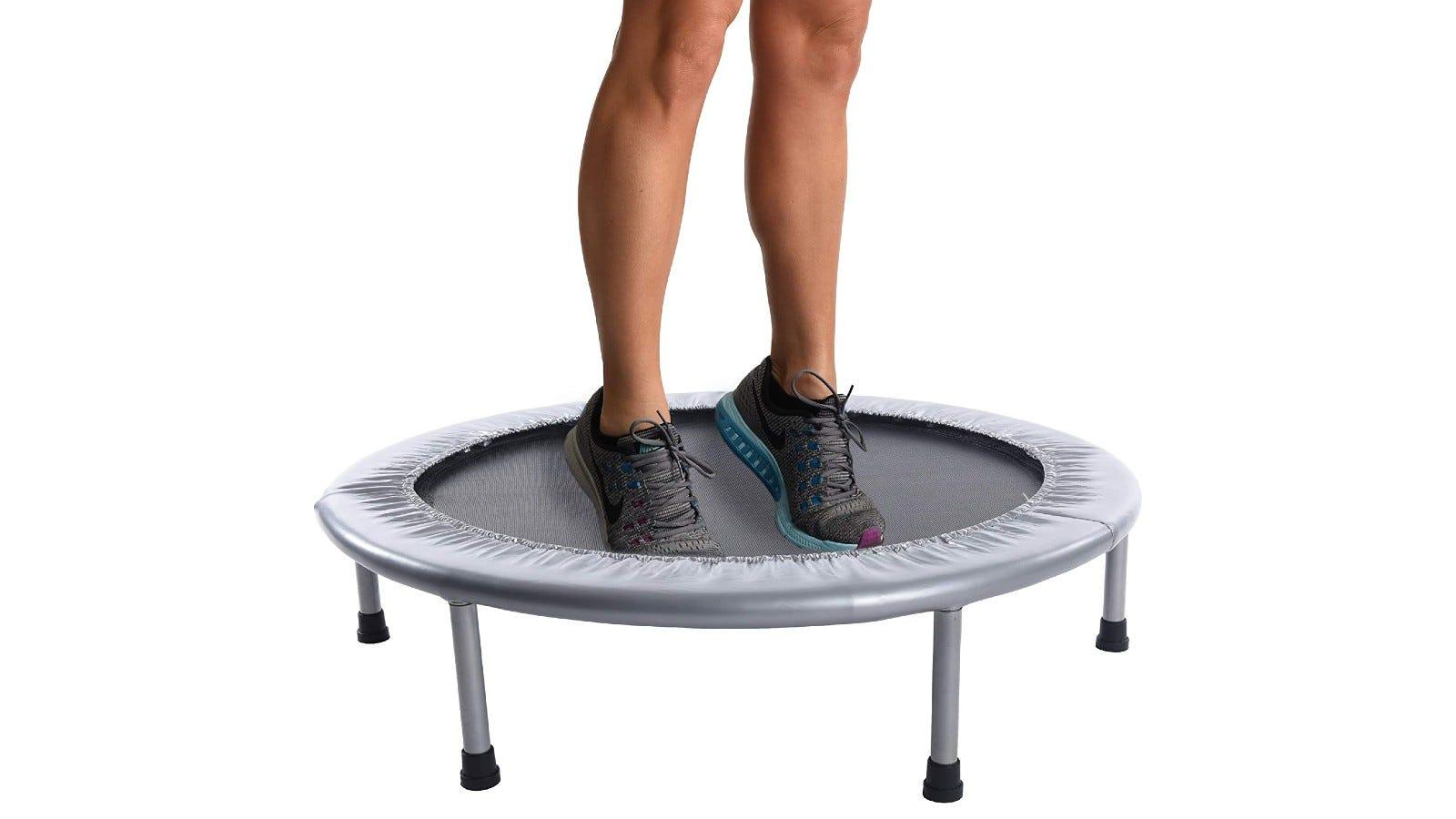 a person's legs on a gray mini trampoline