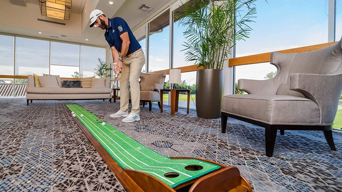 A man practices his putting skills in an office.