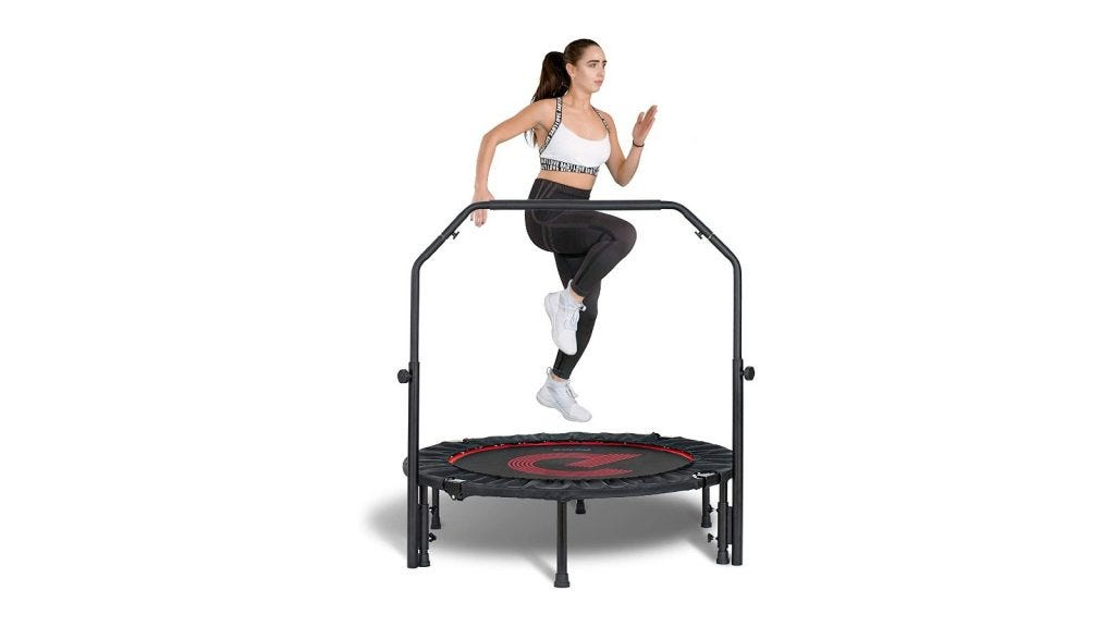 a woman jumping on a mini trampoline with a bar over it
