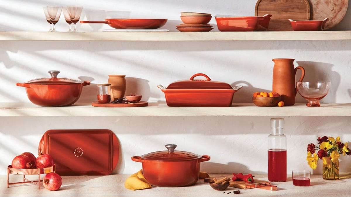 Le Creuset cayenne cookware arranged on kitchen shelves.