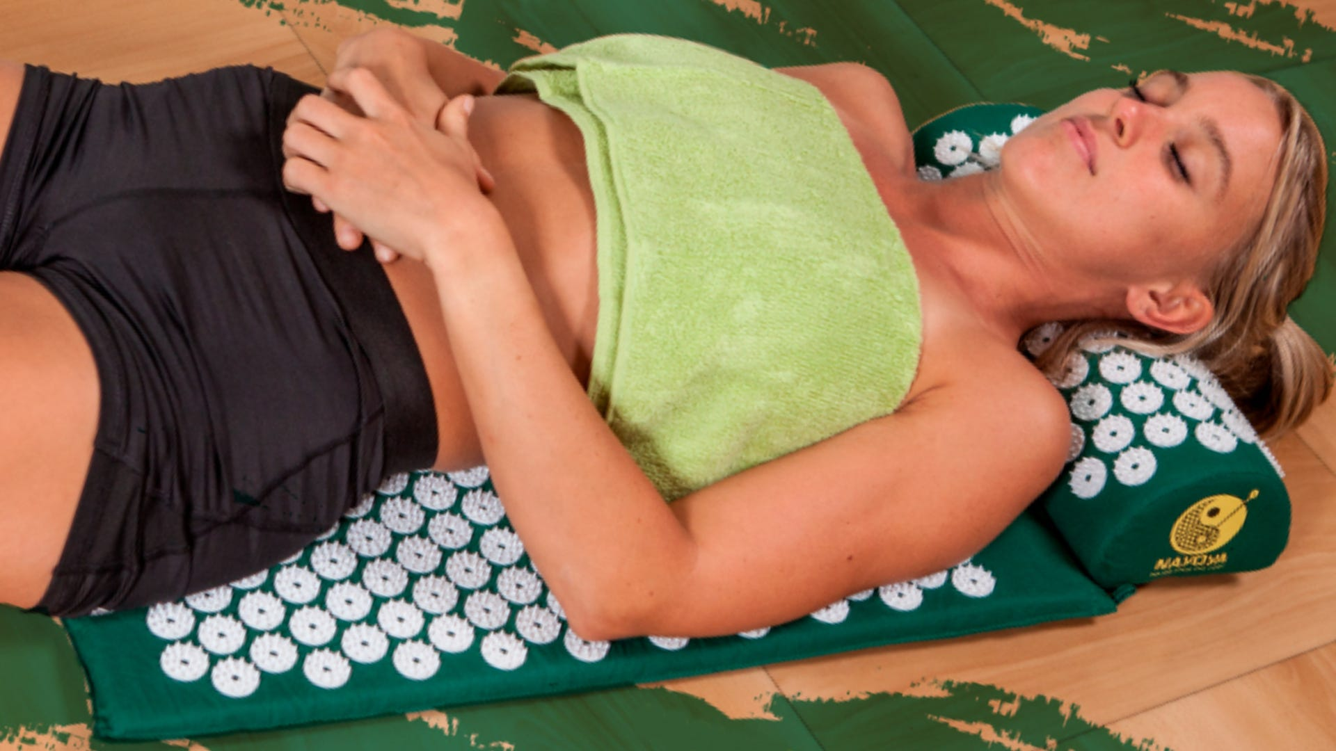 A woman laying on a dark green acupressure mat.