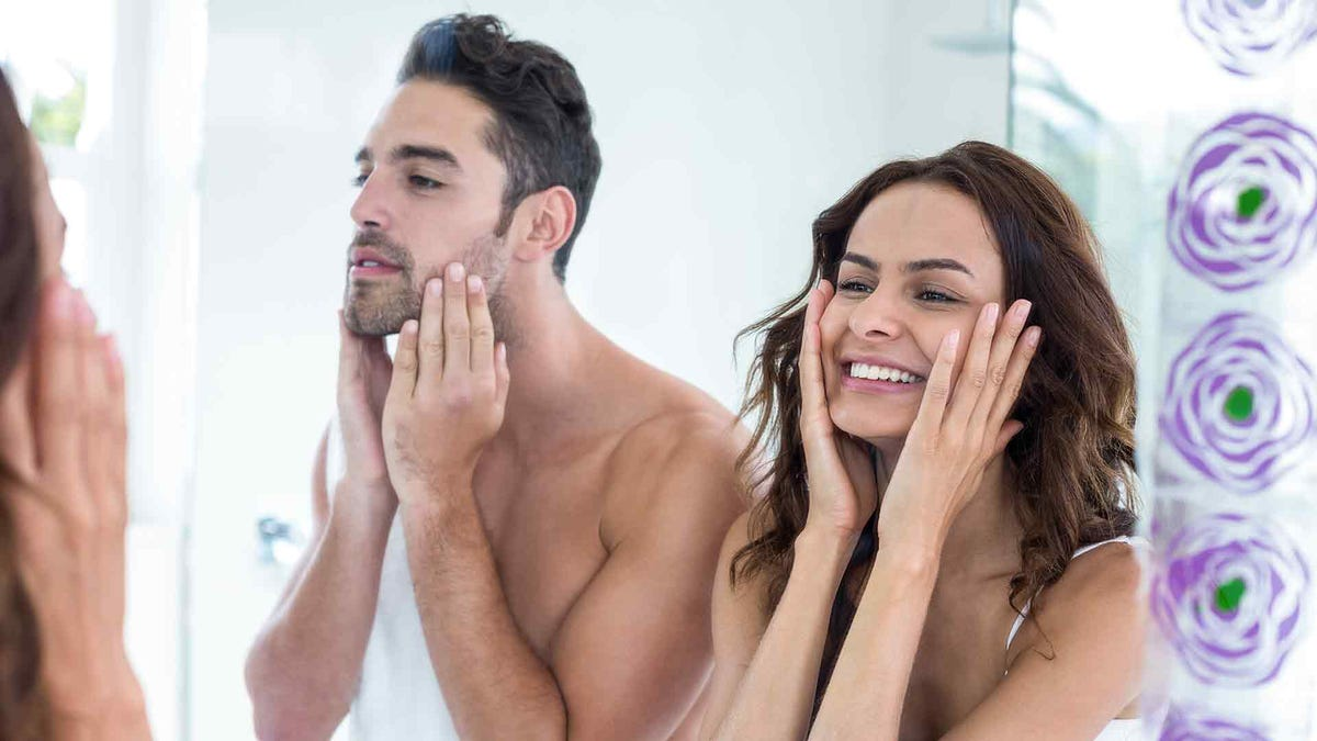 A man and woman washing their faces looking in the bathroom mirror.