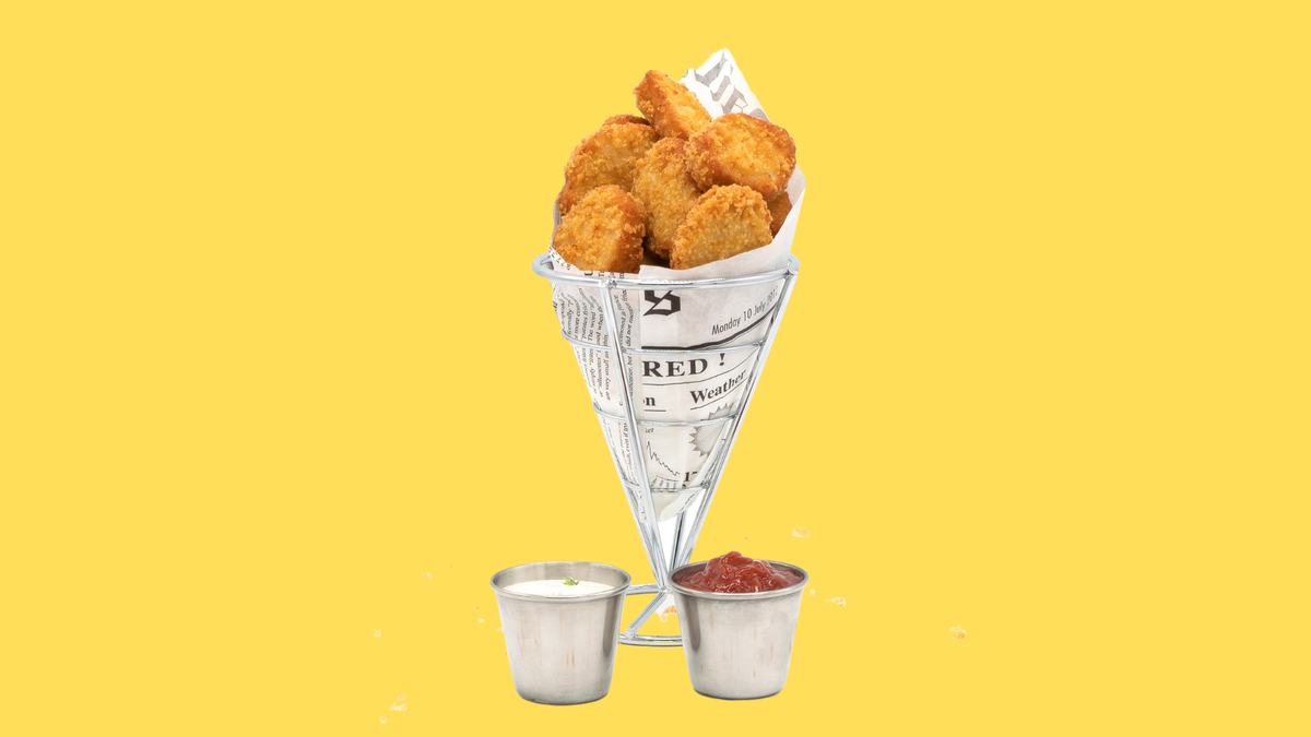 Impossible chicken nuggets wrapped in faux newspaper with two sauces.