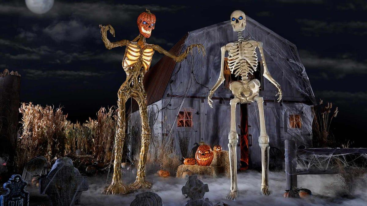 Два скелета опоры Хэллоуина, стоящие перед сараем.