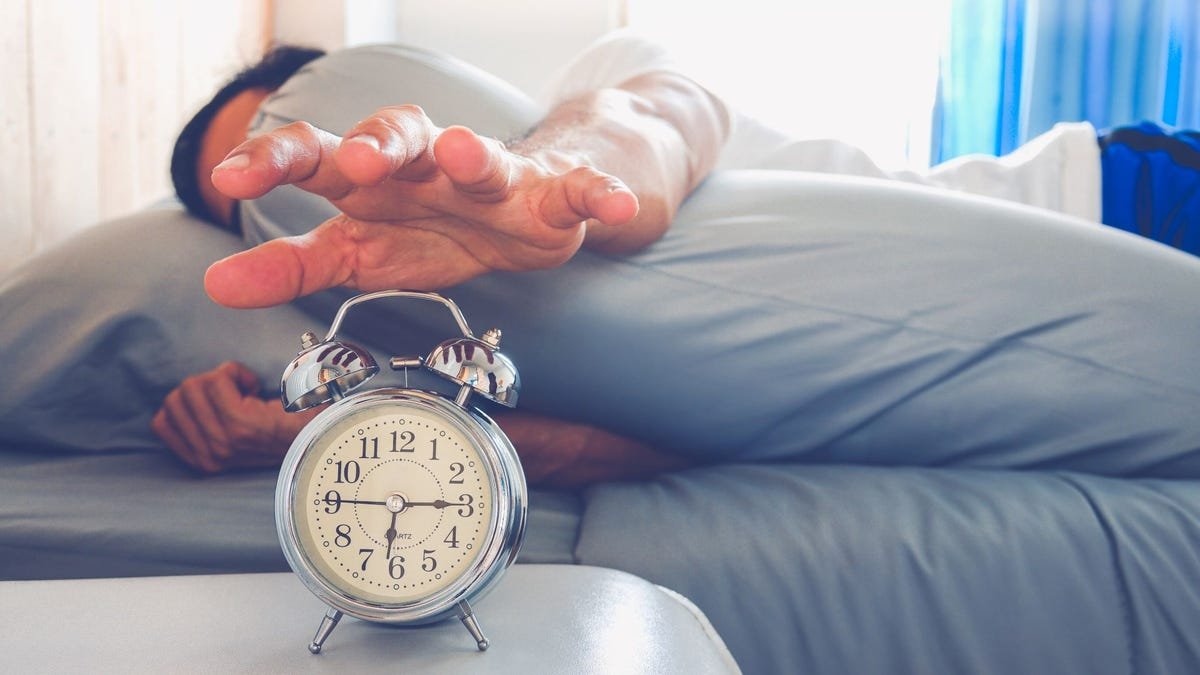 A man in bed reaching toward a blaring alarm clock on a bedside table.