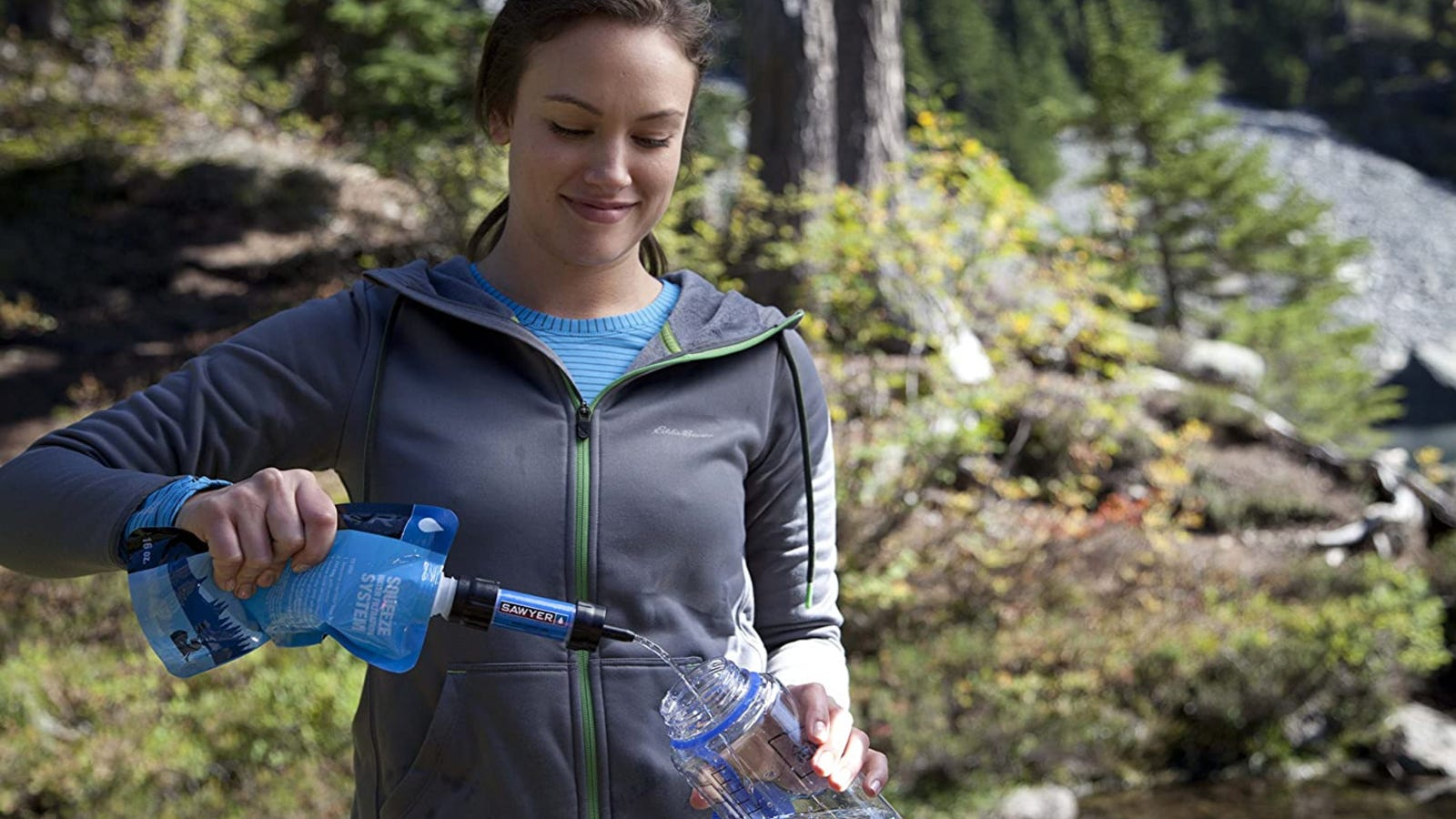 A hiker filling her water bottle with purified water from a sawyer products filtration system.