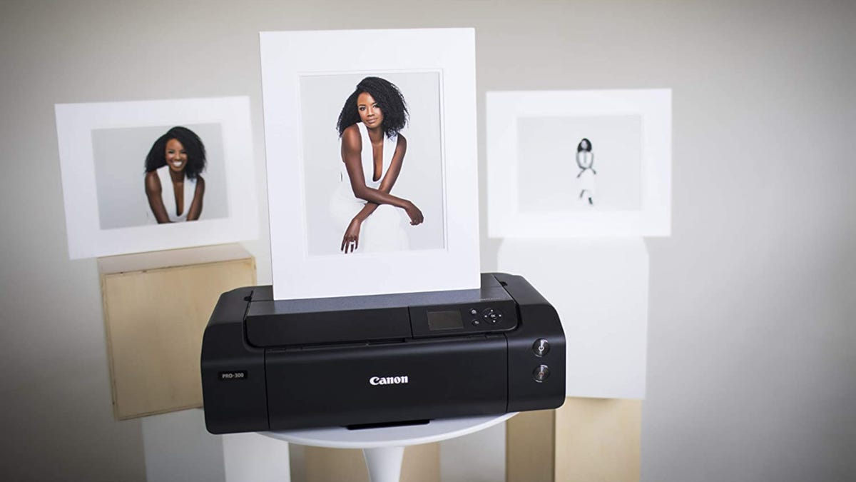 black Canon photo printer with three large printed photos