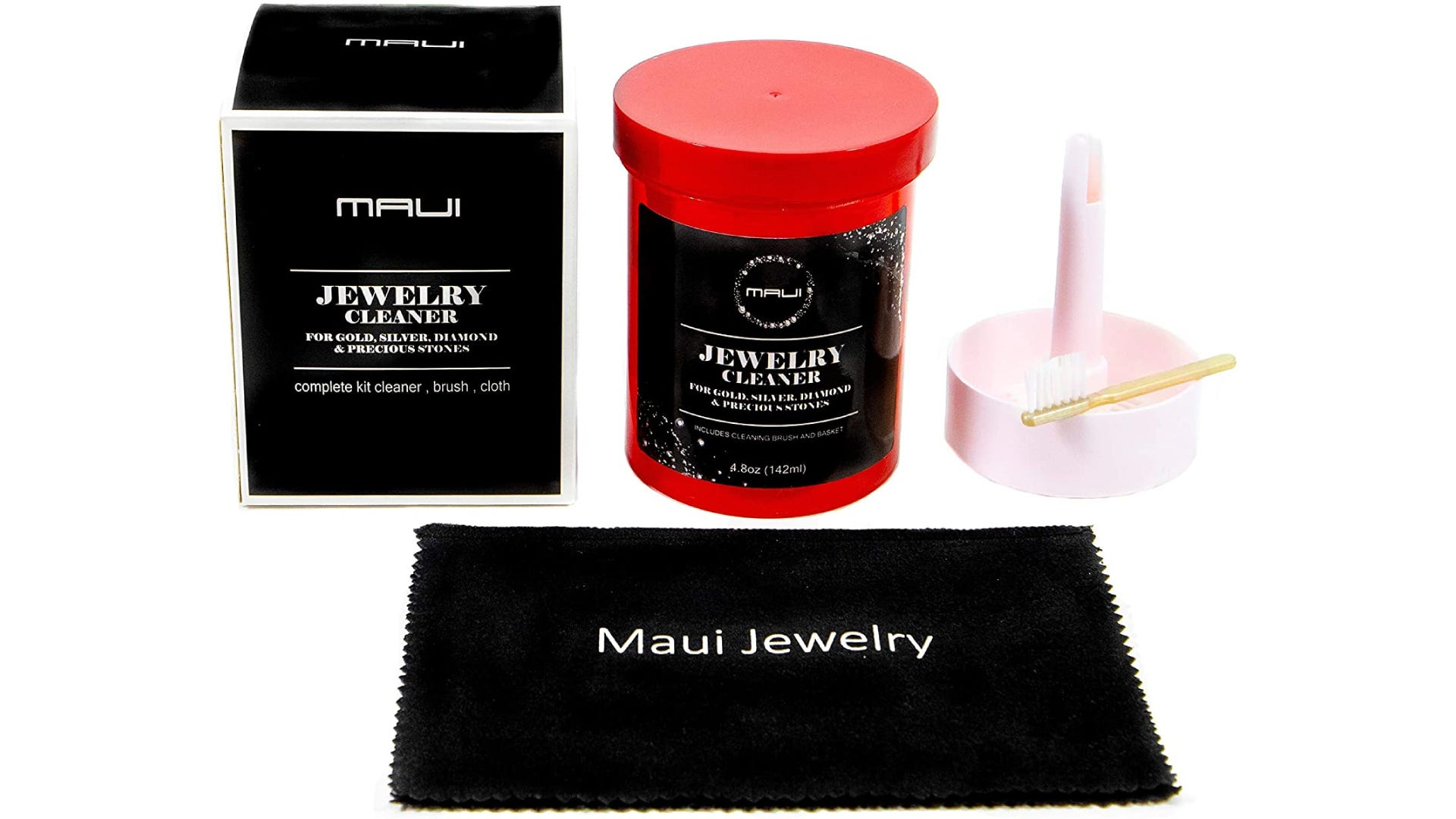 A red container of cleaning solution, a pink stand and brush sit behind a Maui Jewelry cleaning cloth.