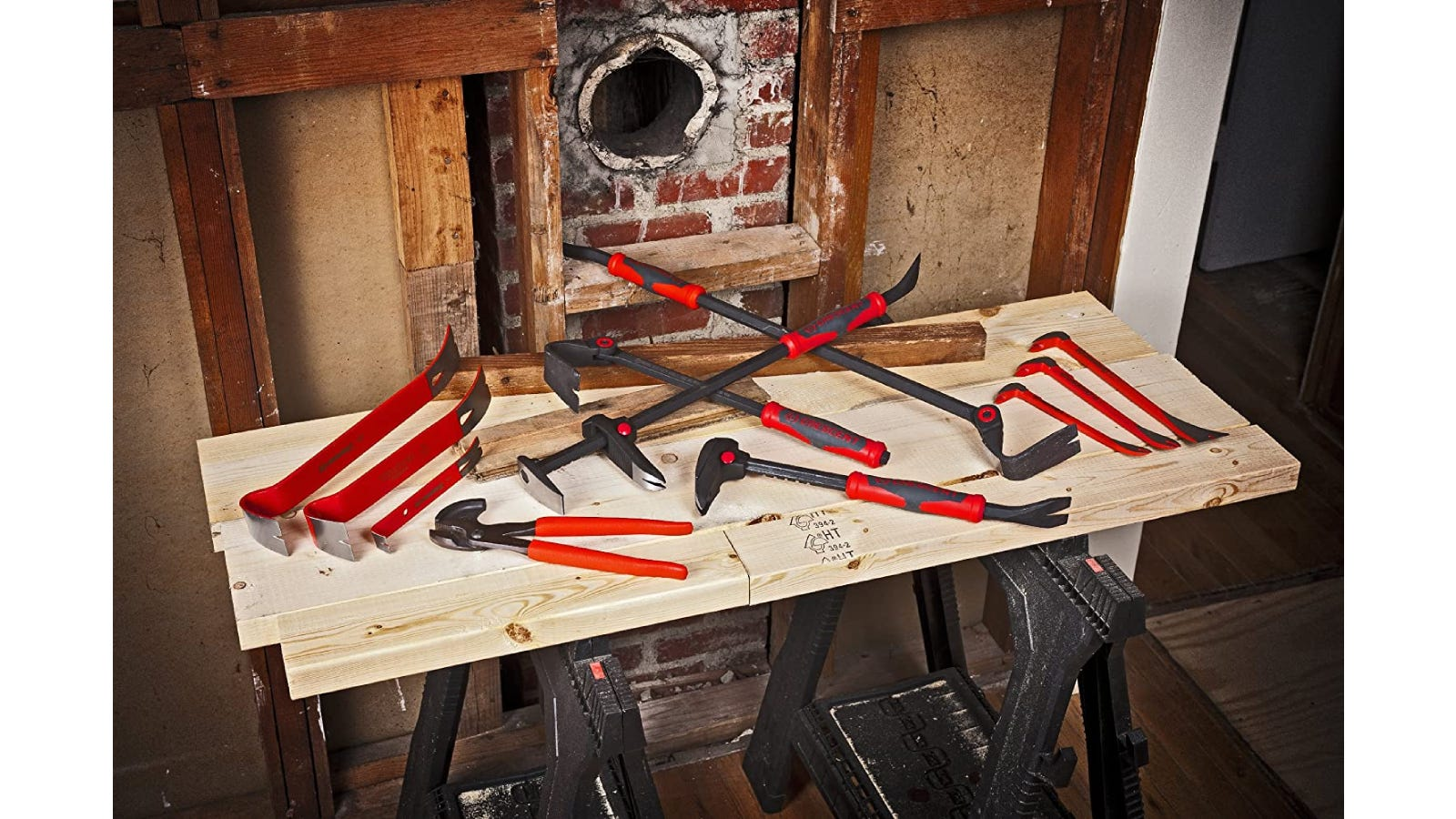 Flat pry bars and other various tools sitting on a wooden work bench.