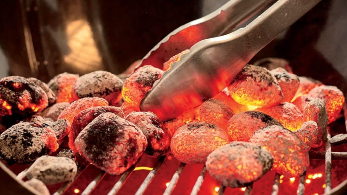 Tongs moving hot charcoals around in charcoal grill