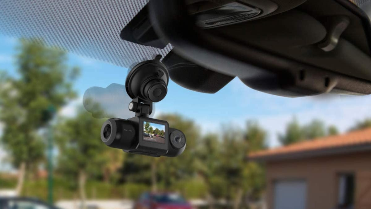 A black dashcam is mounted to a vehicle's windshield.