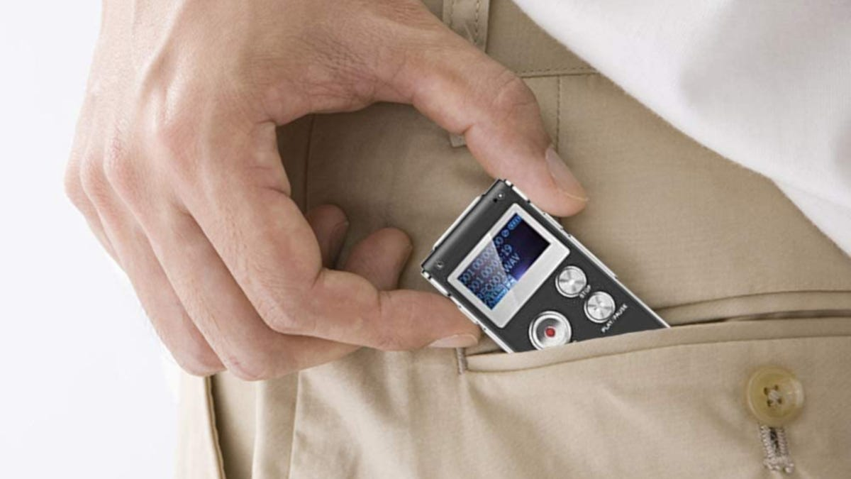 Close up shot of person pulling compact voice recorder out of pants pocket