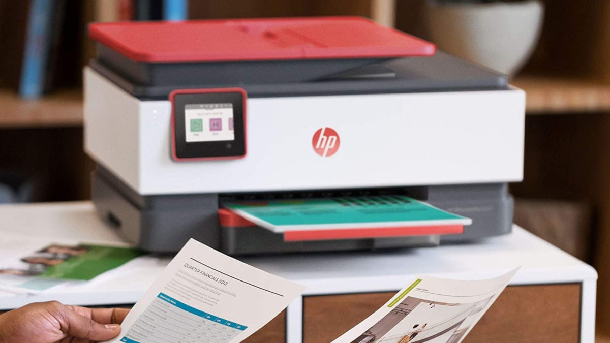 All-in-one printer with fax on a desk in an office printing papers