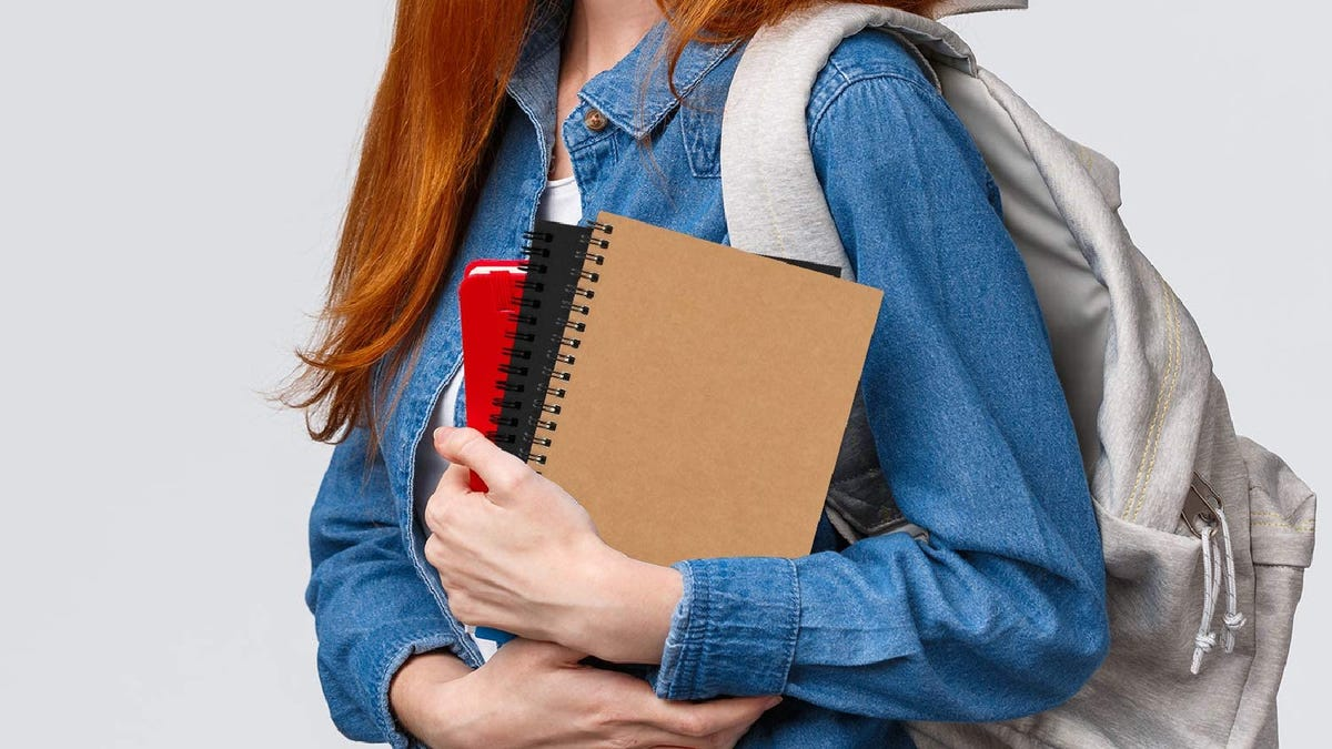 a redheaded young woman wearing a backpack and holding three spiral bound notebooks in her arms