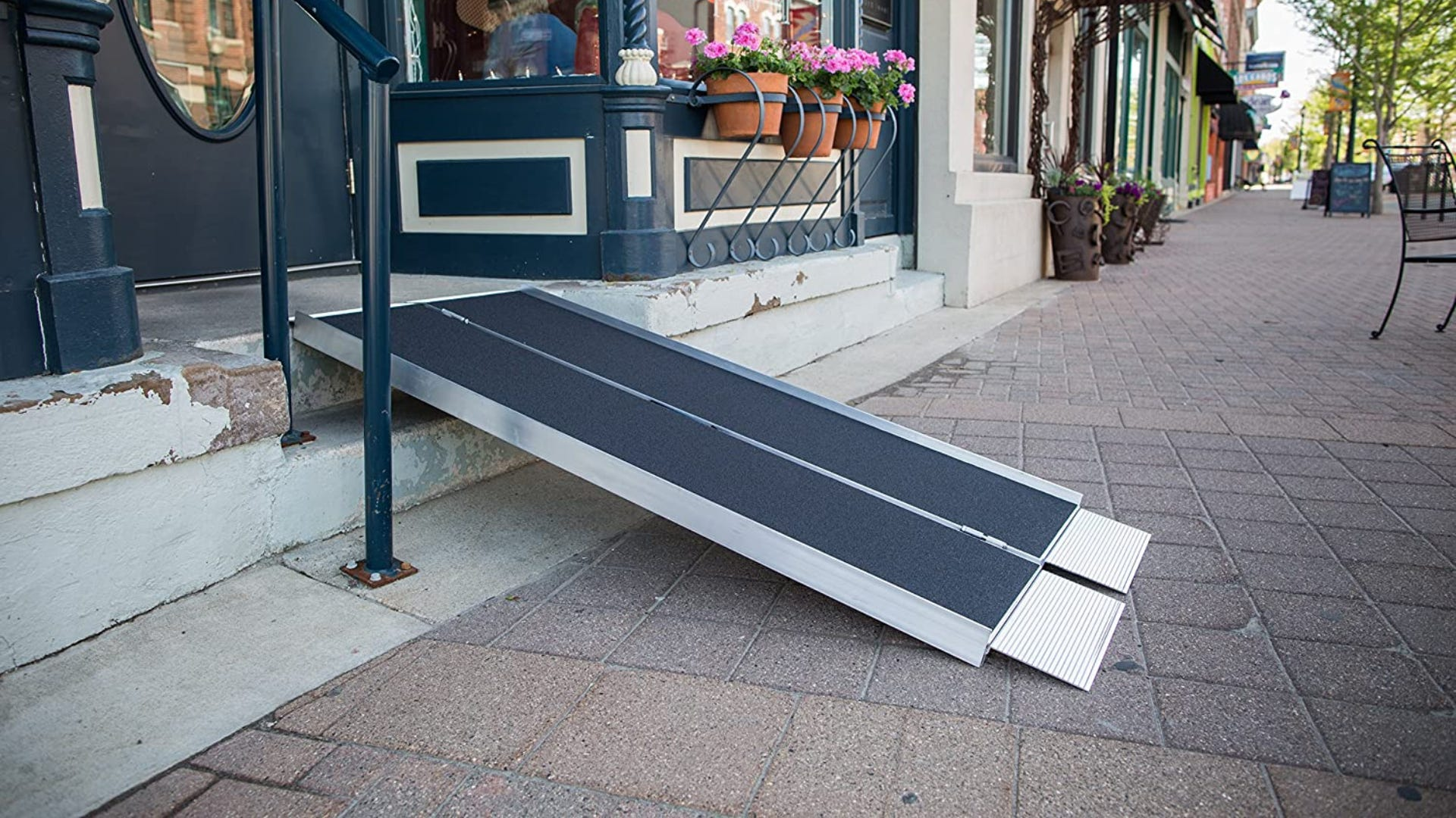 A ramp angled onto outdoor stairs in from of a building.
