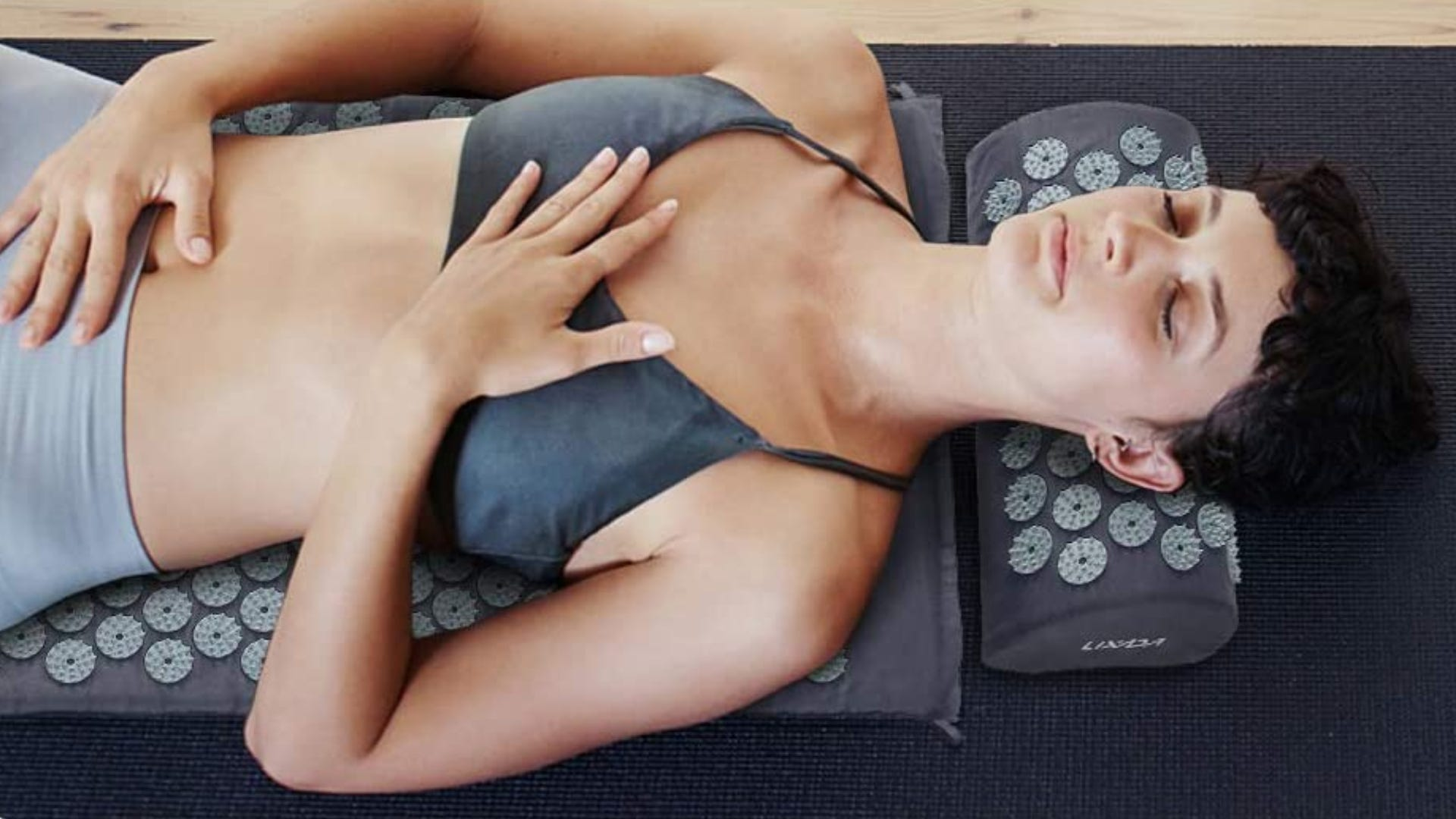 A top view of a woman lying on a grey acupressure mat.