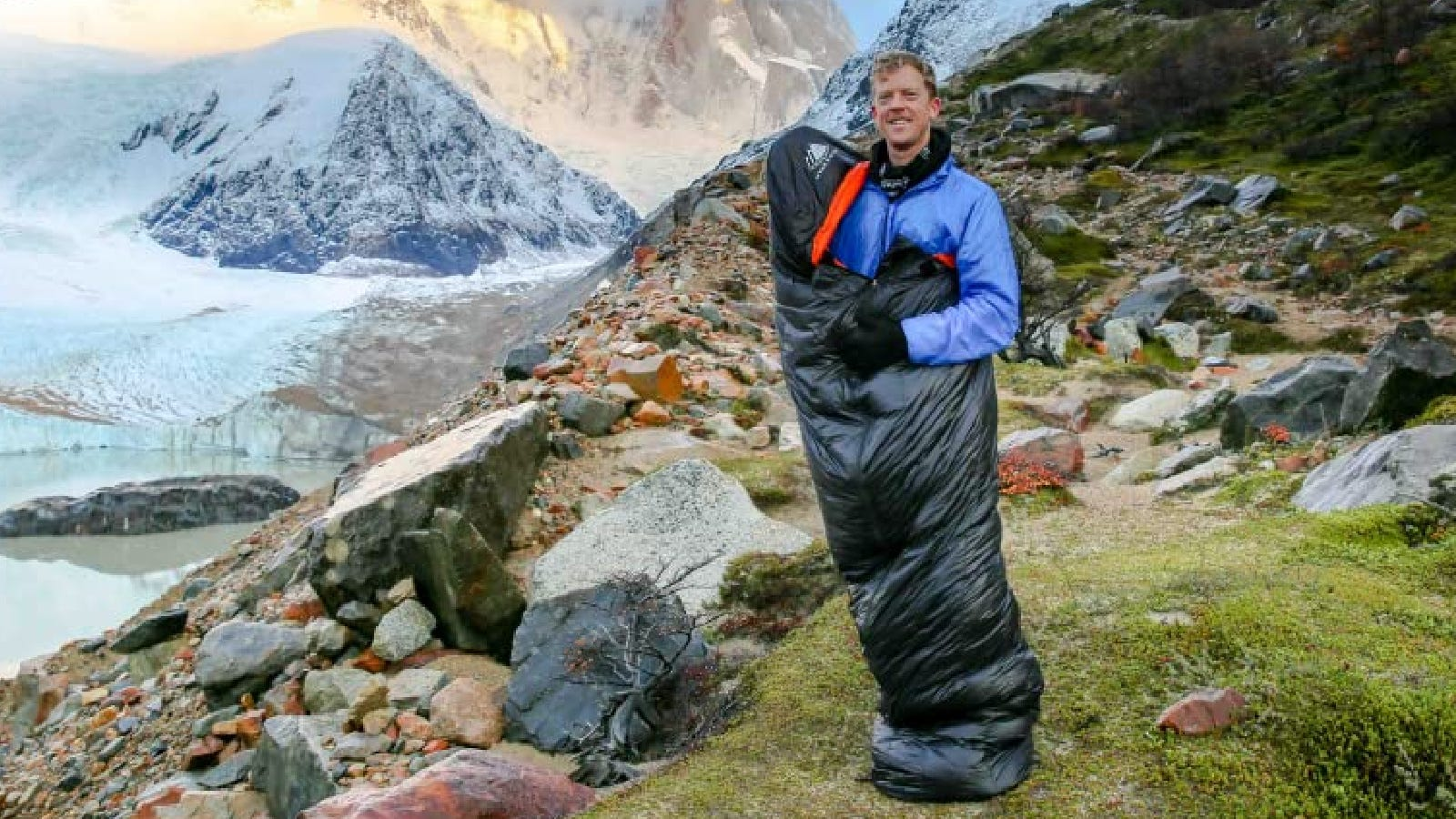 A hiker showing off his new Hyke & Byke mummy sleeping bag with the surrounding views of mountains.