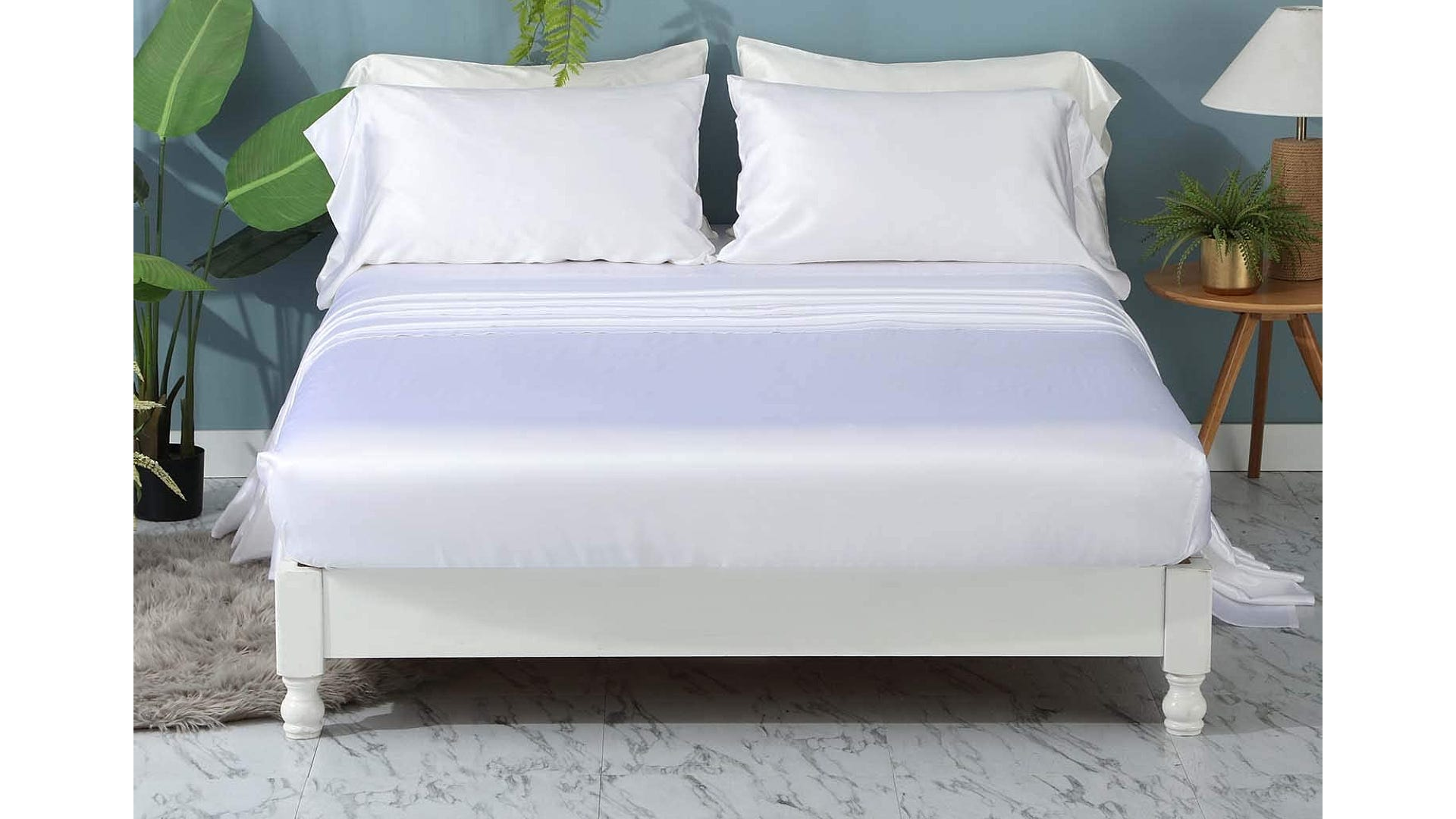 white silk sheets on white bed in bedroom