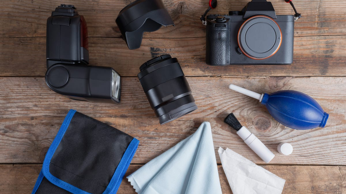 Tools for cleaning camera with dslr camera and lens, flash, pen brush with accessory kit bag.