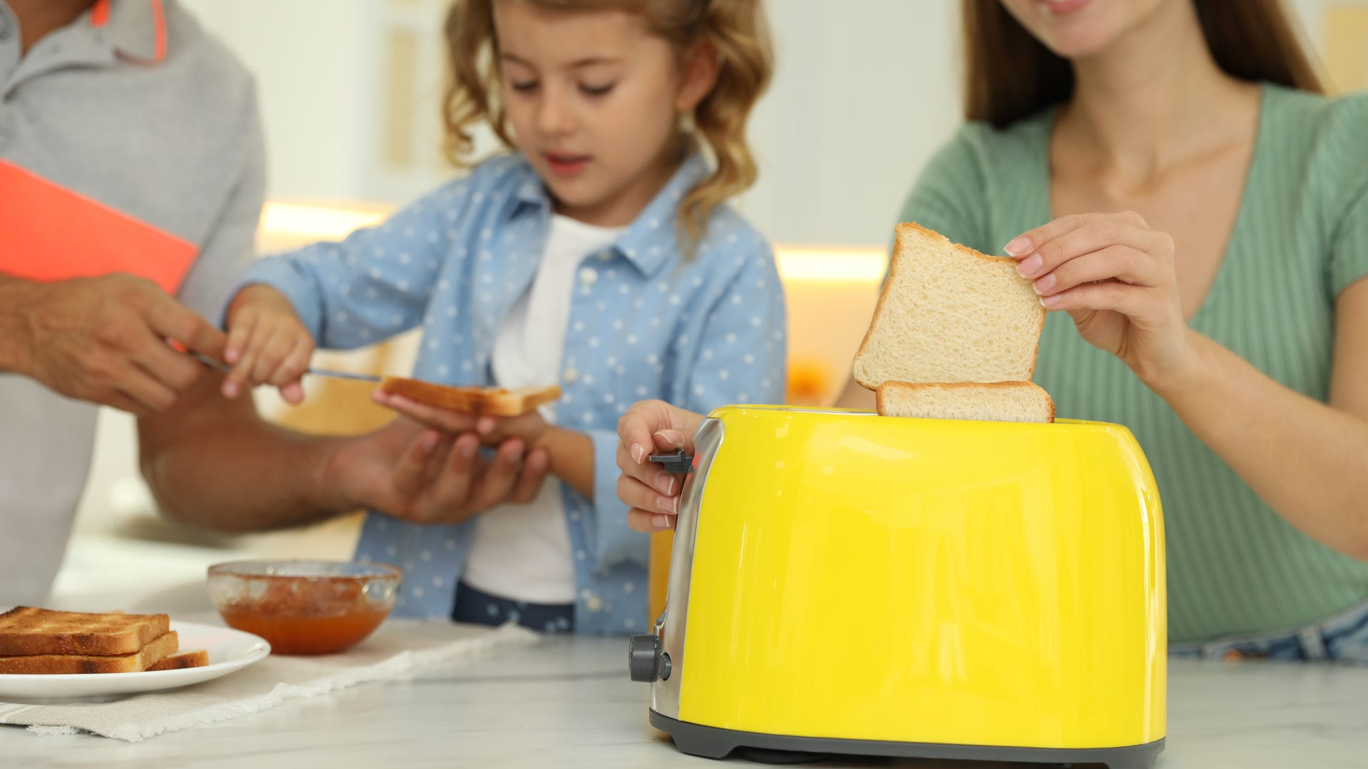 A family uses a yellow toaster to make toast for breakfast.