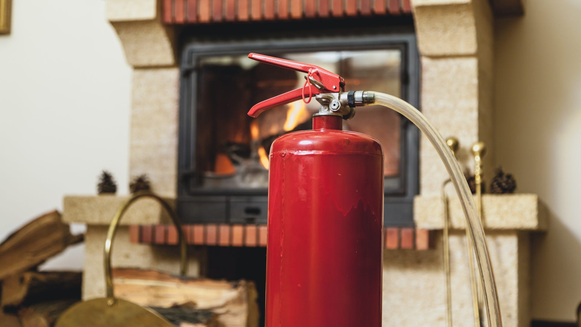 A fire extinguisher stands with a fireplace in the background.