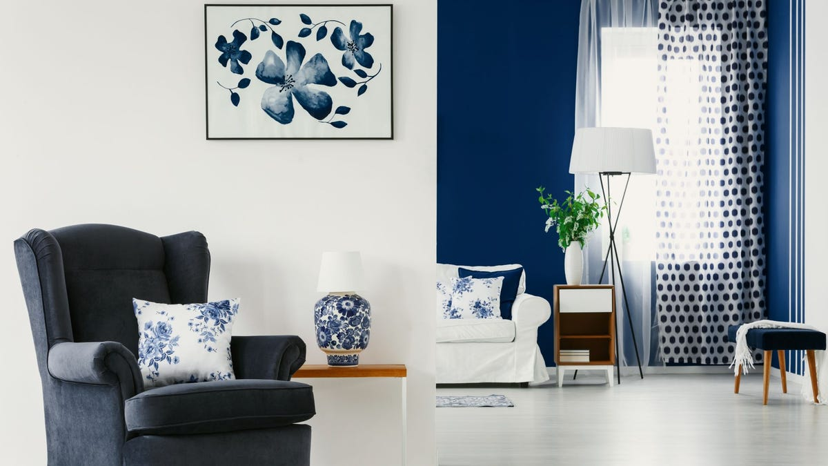 A floral painting and accents in a blue and white living room.