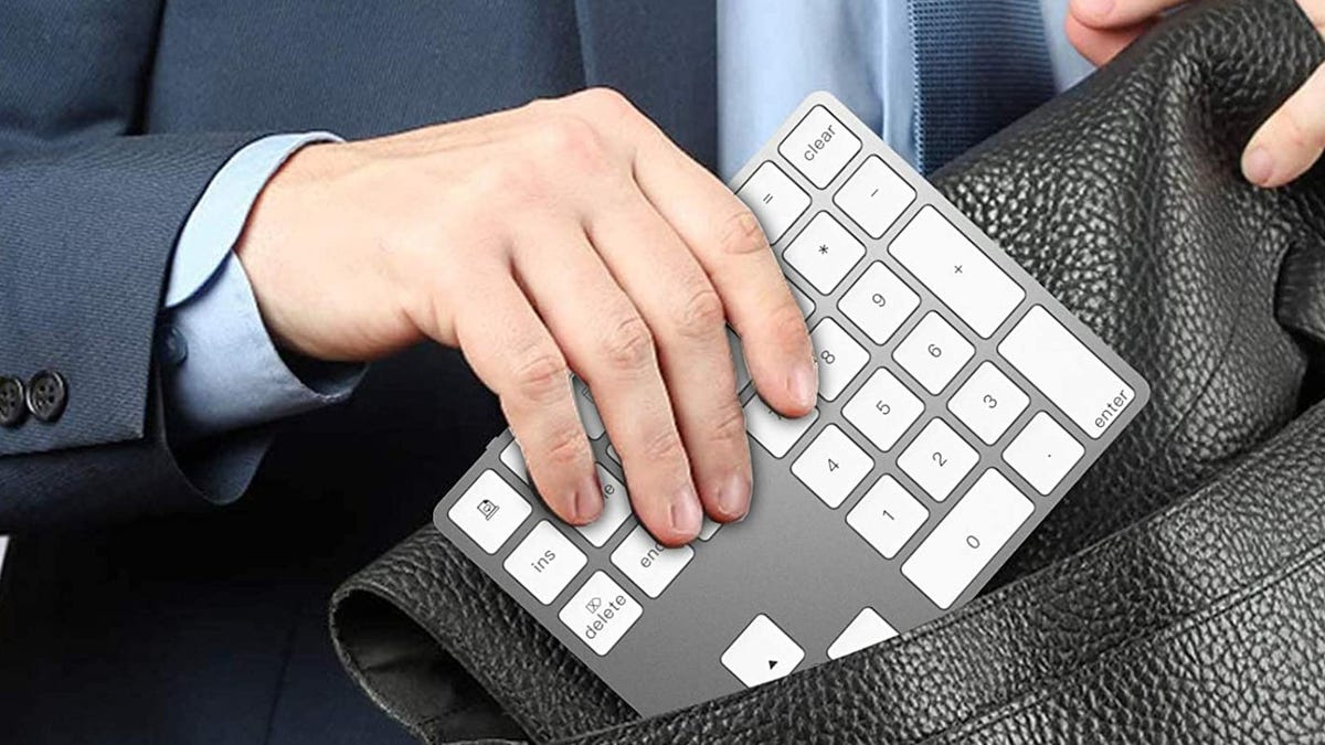 A man storing a numeric keypad in his travel bag
