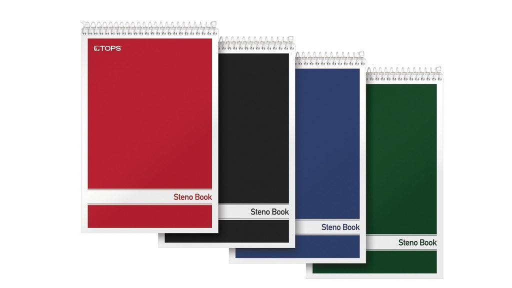 stacked red, black, dark blue, and green top-flip spiral notebooks