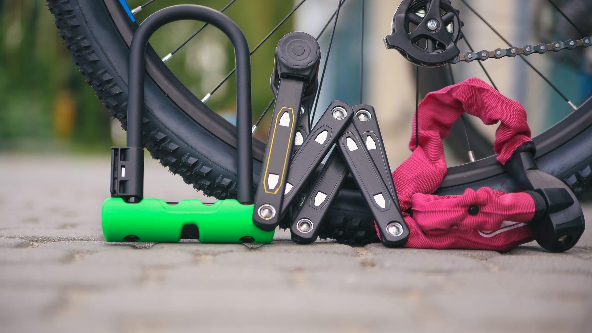 Three different types of bike locks rest by a bike tire.