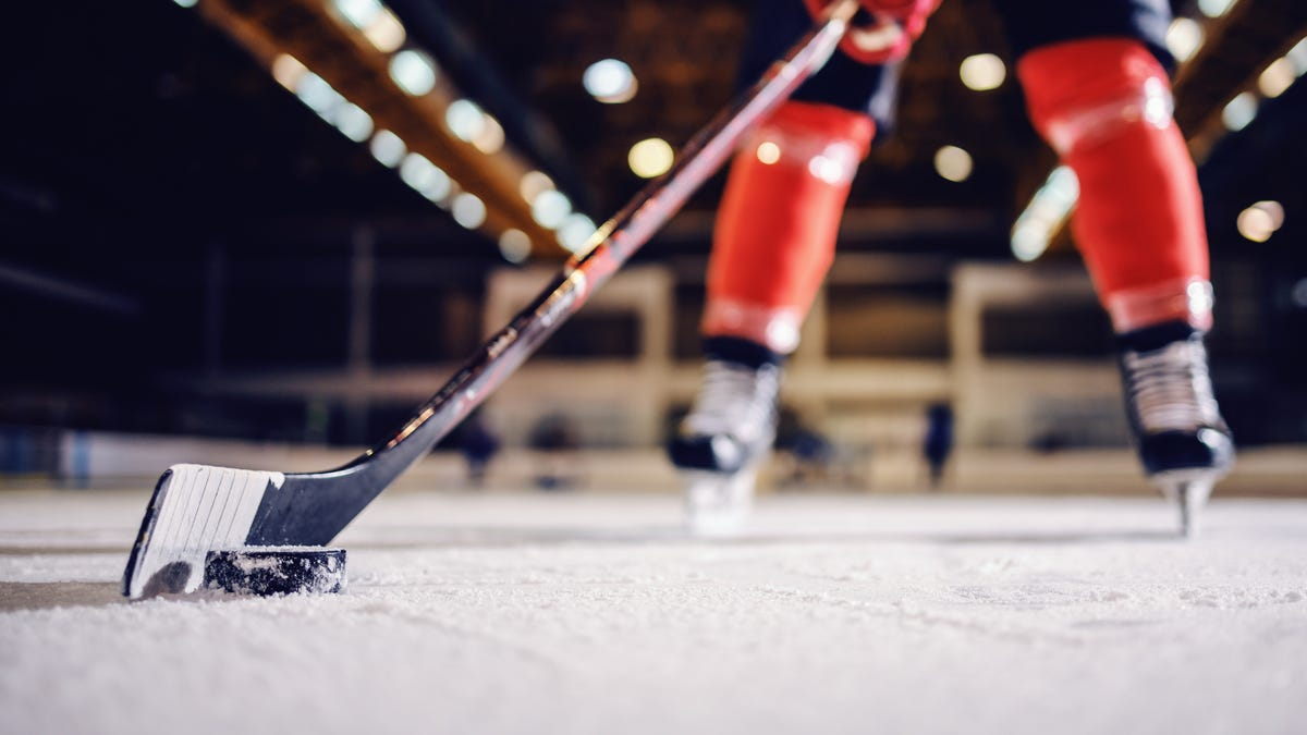A close-up of a hockey player skating with a stick and a puck.