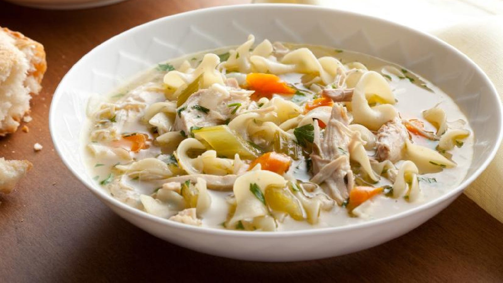 A bowl of hot chicken noodle soup filled with celery, carrots, egg noodles and parsley.