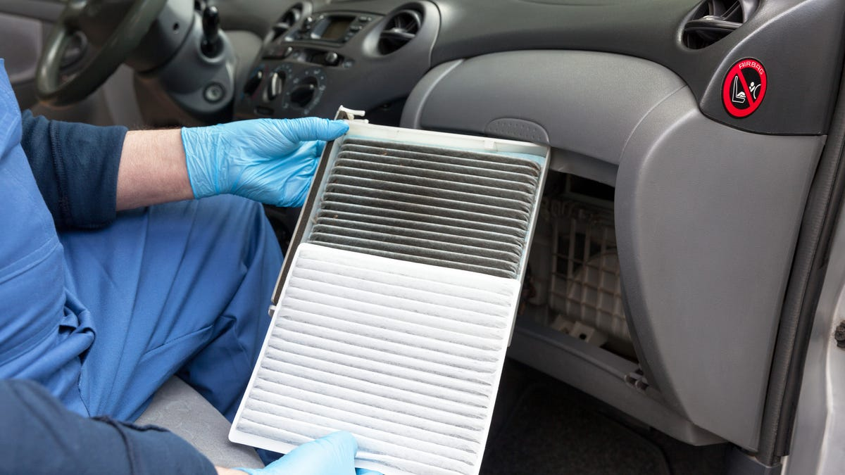 a person holding a clean and dirty car cabin air filter inside the car