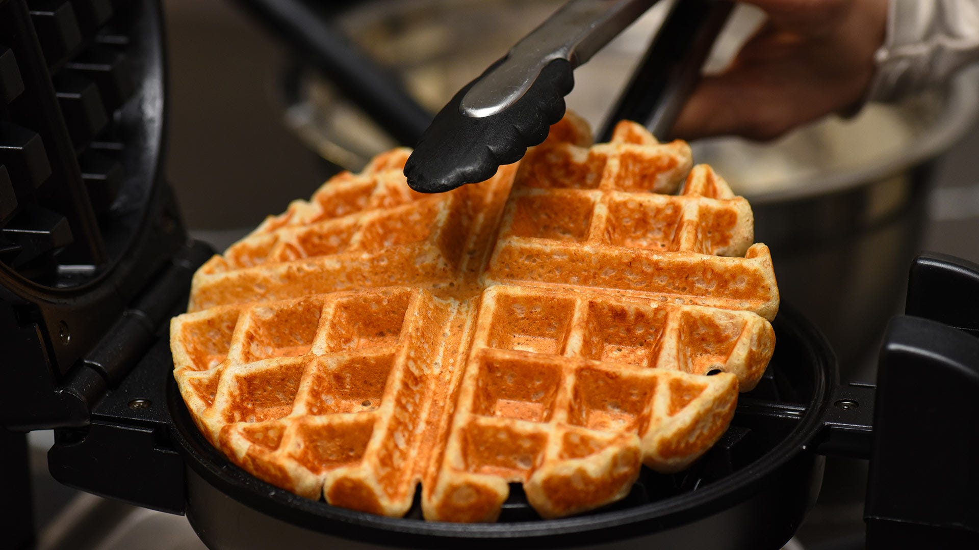 A man removing a fresh waffle from a waffle iron using silicone tongs.