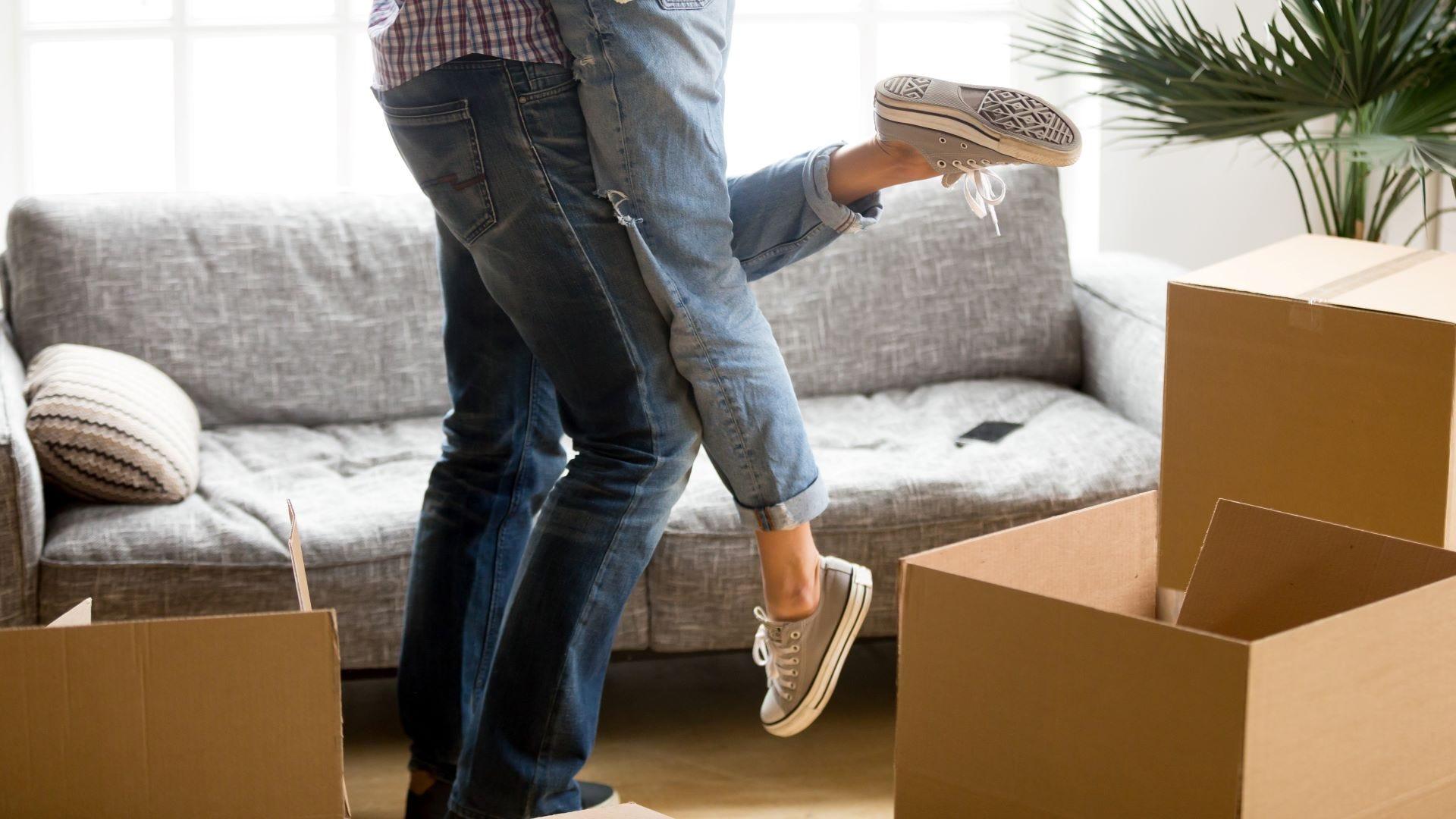 Man lifting woman among cardboard boxes on moving day.